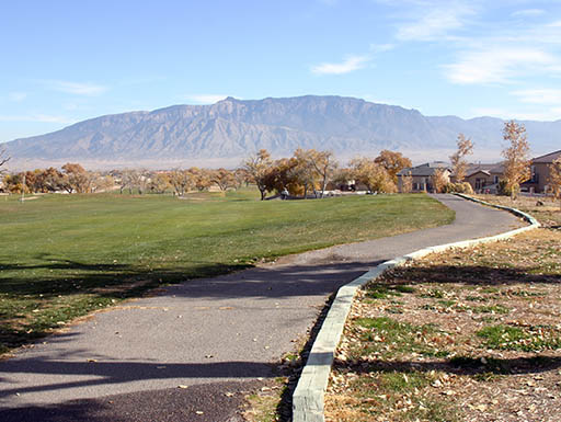 A paved golf cart path curves through a golf course
