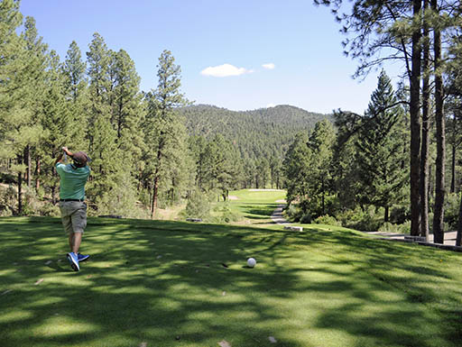 Man tees off at a treed golf course surrounded by the Sandia mountains of Albuquerque, New Mexico