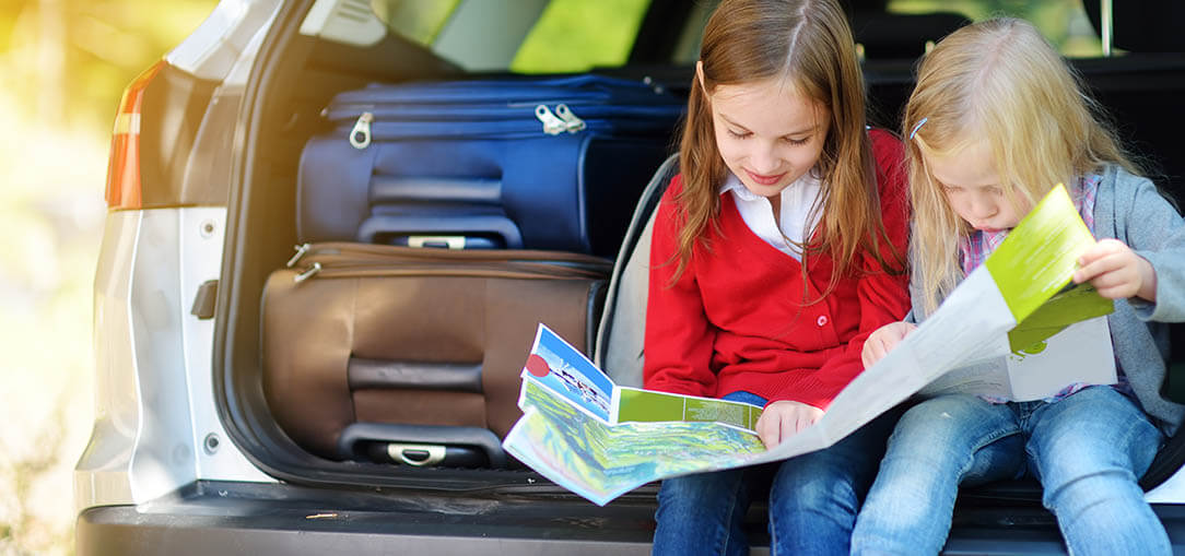 Two young girls sit beside each other in the back of a grey vehicle looking at a map, while luggage sits beside them as they prepare for a roadtrip