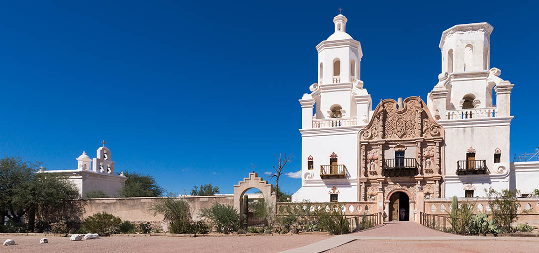 White building of Mission San Xavier del Bac against a bright blue sky in Tucson, Arizona
