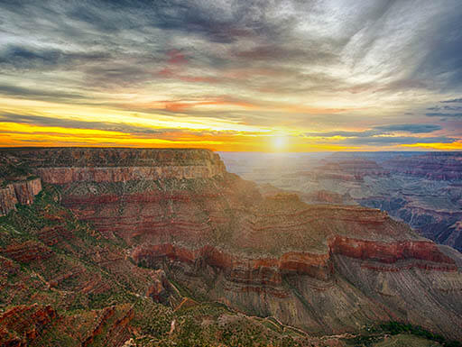 The Grand Canyon is pictured at sunset, with the bright sun setting in the background, illuminating an orange, blue, and white sky above the canyon.