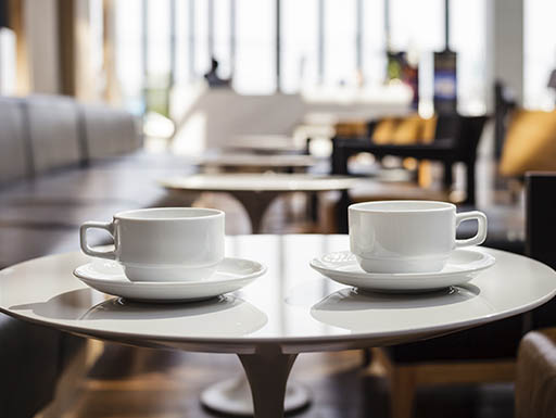 Two coffee cups siting on a table in a cafe