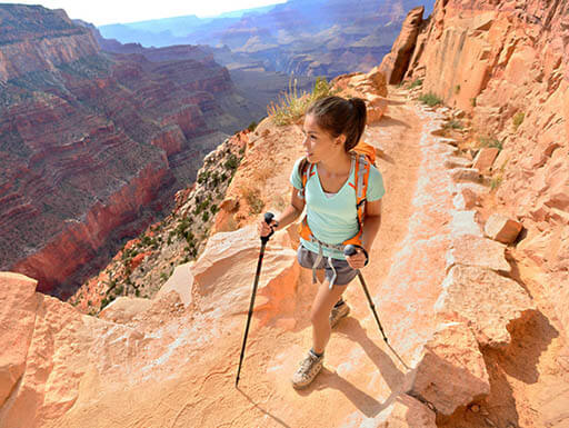 A young, female hiker is pictured on the bright orange cliff of the Grand Canyon in Arizona, going on a beautiful morning hike.