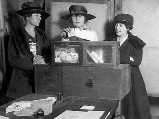 Women in New York State are seen in a black and white photo while voting legally for the first time in 1917.