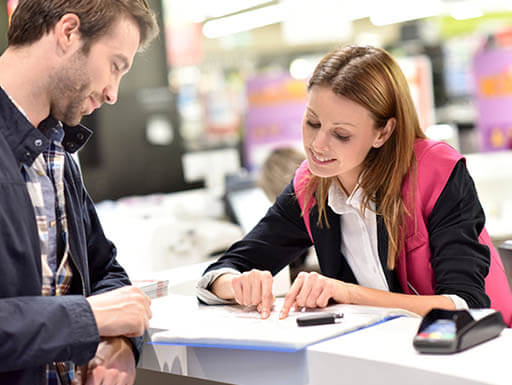 A man at a car rental counter discussing the rental agreement with a rental employee