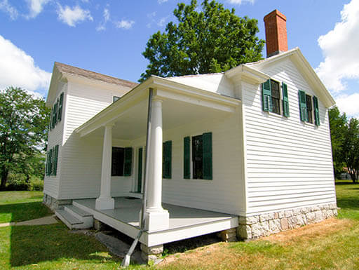 The white exterior of Elizabeth Cady Stanton's house is pictured on a green yard with leafy green trees and a blue sky in the background in Rochester, NY.