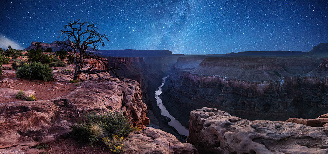 The Grand Canyon is pictured at night, with a river running below the canyon and a stunning night sky filled with stars and constellations.