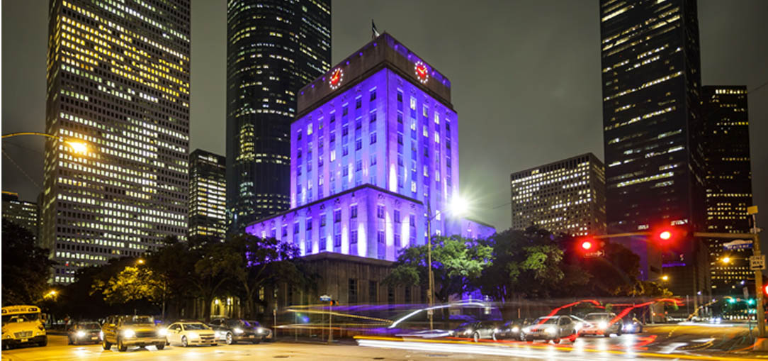 Houston's City Hall Building at night with traffic passing