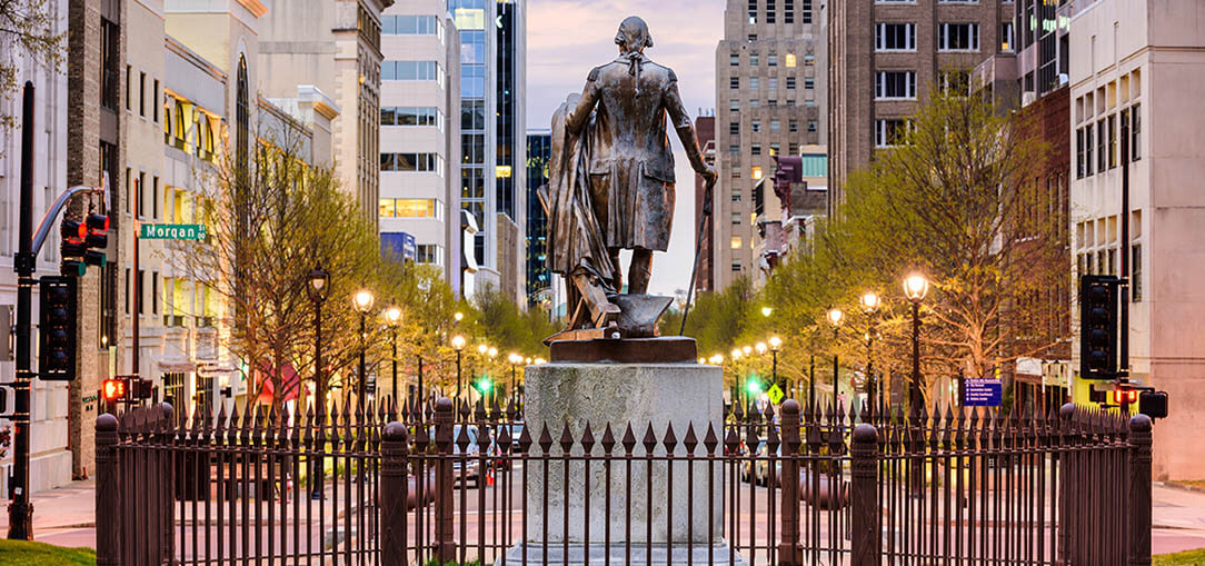The back of the George Washington statue is seen surrounded by a wrought iron fence with the downtown cityscape in the background during sunset in Raleigh, North Carolina