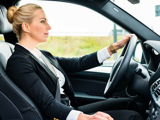 A blond, female business traveler in a black and white suit is pictured driving in a vehicle while on a business trip