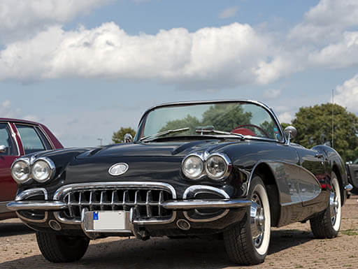 A polished black convertible corvette on display at a classic car lot