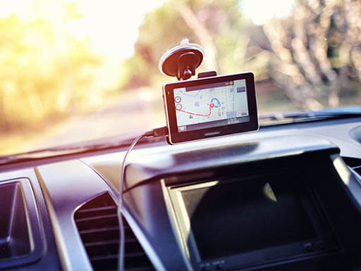 Close-up of dashboard inside vehicle with GPS device attached to the windshield showing map navigation