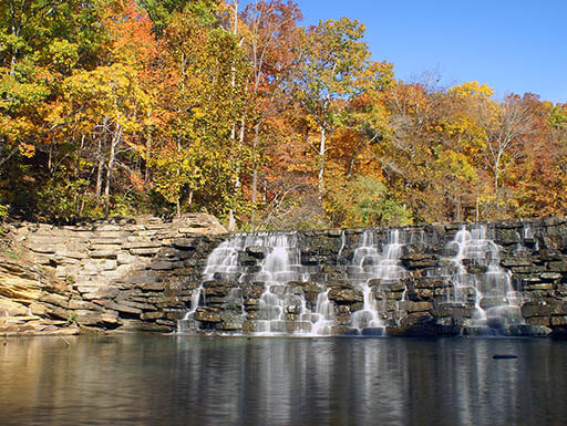 Tranquil cascading waterfalls with beautiful fall foliage at Devil's Den State Park in Arkansas
