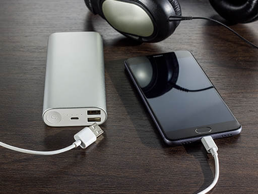 A cell phone, travel charger and headphones are pictured with charger cords on a dark brown wooden desk as a business traveler prepares their technology for their trip