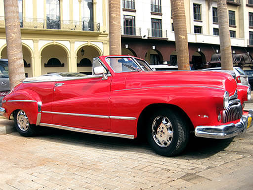 A shiny red classic convertible car in a parking lot in Havana, Cuba