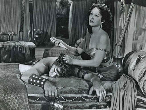 Black and white still from the film Samson & Delilah shows Hedy Lamarr and male co-star, Victor Mature, in a scene