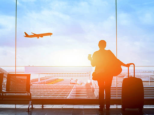 The silhouette of a business traveler is pictured looking out of an airport window, as an airplane takes off in front of a light blue sky