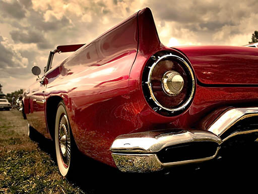 A close-up view of a vintage red car's rear bumper in a field on a sunny day