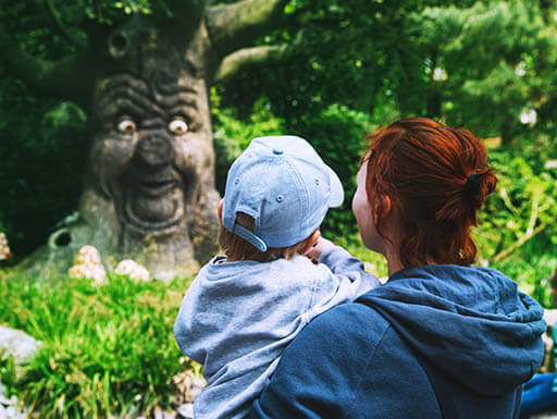 A family enjoying a day out at Efteling them park, in front of a fairy tale tree