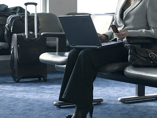 A female business woman is pictured in a suit with a laptop on her lap and a cell phone in her hand as she waits for her flight in an airport during a business trip