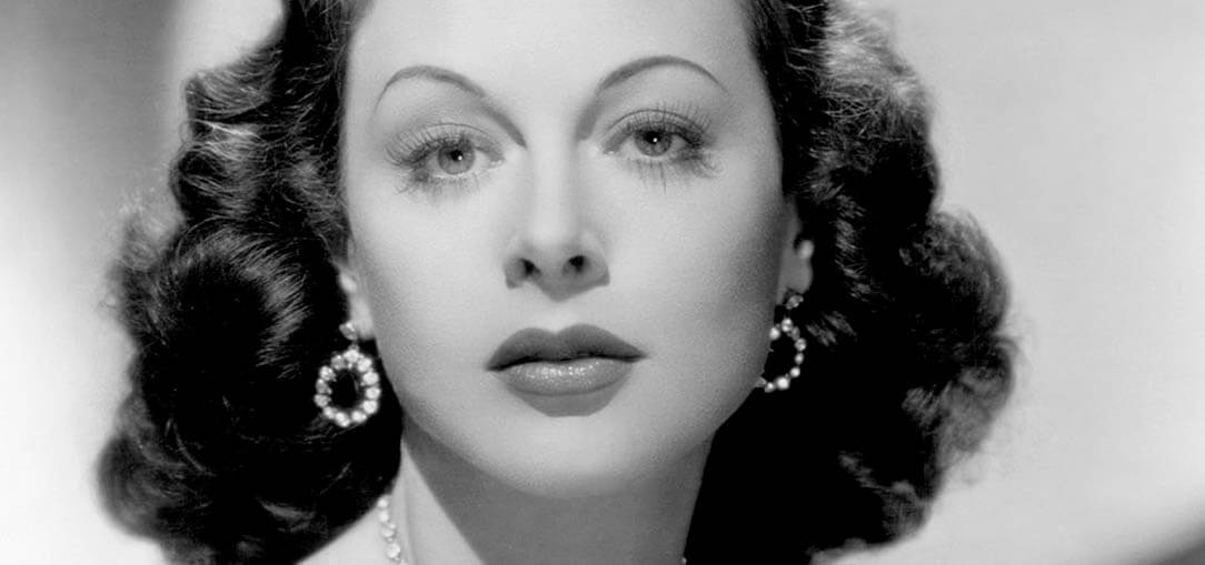 Black and white head and shoulder portrait of Hedy Lamarr in an off the shoulder dress and stunning jewelry