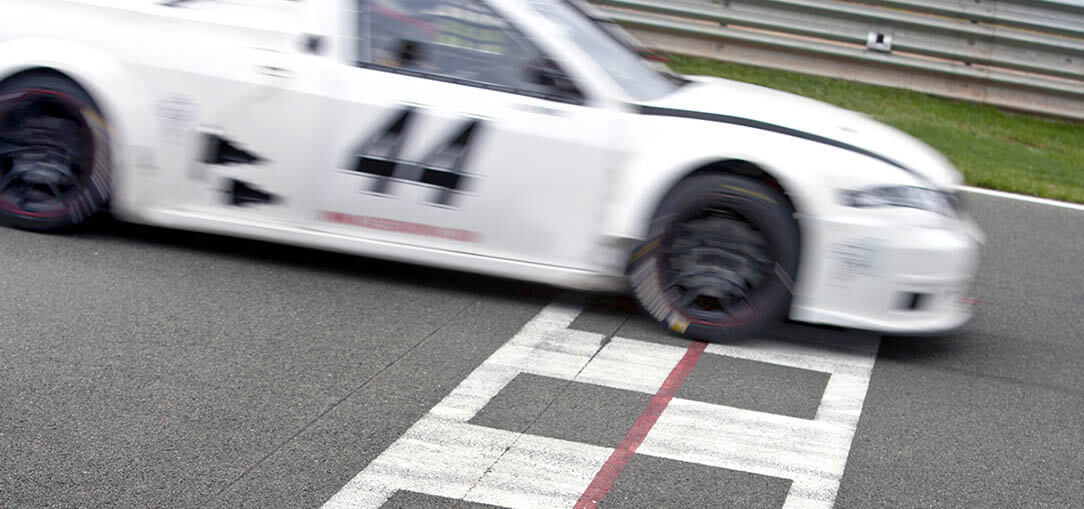 White race car crossing the finish line