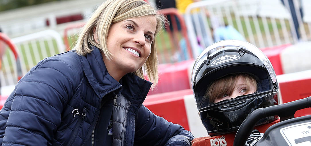 Racing driver, Susie Wolff, looks on as she kneels next to child wearing a helmet in a go cart.