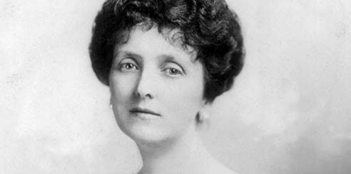 Black and white portrait of Emily Post wearing a formal dress with lace sleeves.