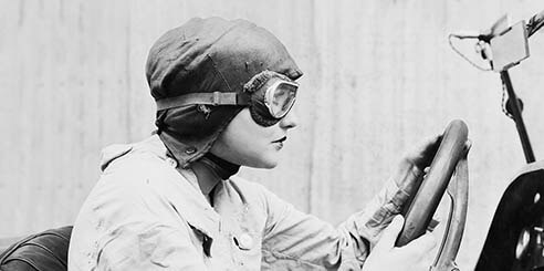 Early black and white portrait of a female racecar driver wearing a cap, googles and race suit from the side profile in a topless car.