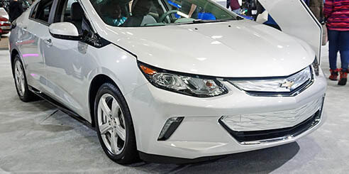 Front view of a silver 2017 Chevrolet Volt hybrid car on display at an auto show on a busy afternoon.