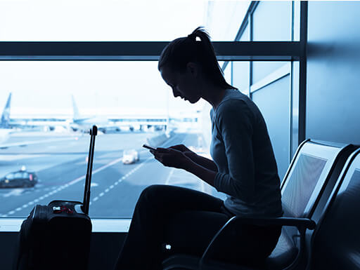 Silhouette of a woman using a mobile phone while sitting next to a window in an airport