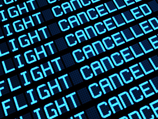 Close up of digital airport sign reading 'Flight Cancelled
