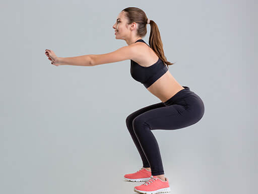 """=""""A side view of an athletic woman in black with pink shoes doing squats in workout clothing."""