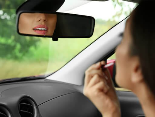 A woman applies lipstick in the rearview mirror of a car while driving to work on an early morning.