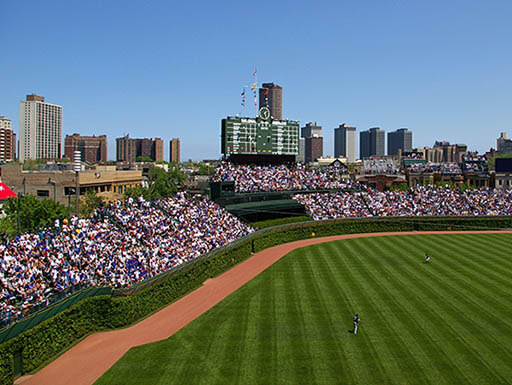 The bright green grass on Wrigley Field is pictured, with crowds surrounding it and the skyline of Chicago in the background on a Spring afternoon.
