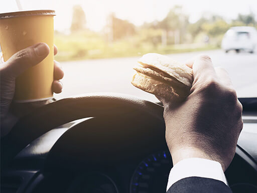 A man drives dangerously while holding a coffee cup in one hand and a breakfast sanwich in the other in traffic during rush hour.