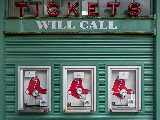Close-up view of the Boston Red Sox ticket office windows, surrounded in green under a red light sign that says Tickets and another painted white sign for Will Call