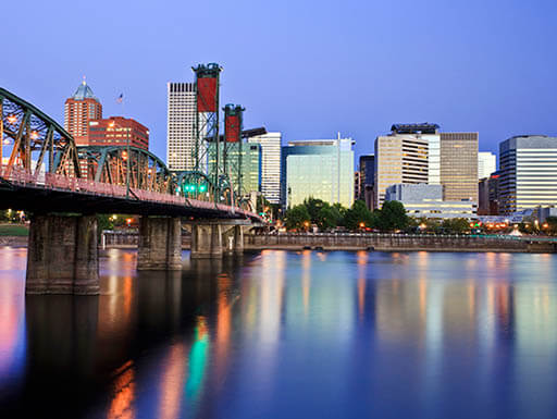 View of a bridge, with the reflection of the city over water leading into Portland, Oregon, at twilight
