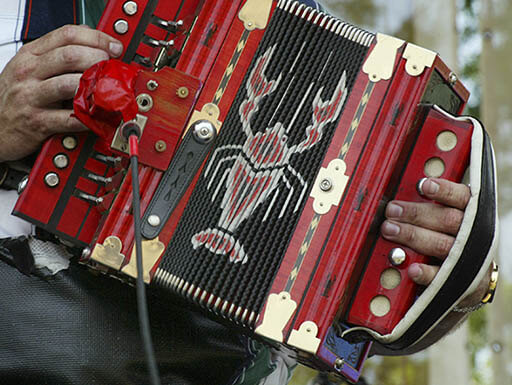 Hands play a crawfish-decorated accordion at Buck and Johnny's restaurant in Louisiana on a summer evening.