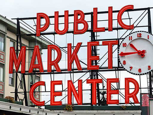 Large outdoor sign at Pike Place Market reads 'Public Market Center' next to a clock showing 10:45AM.