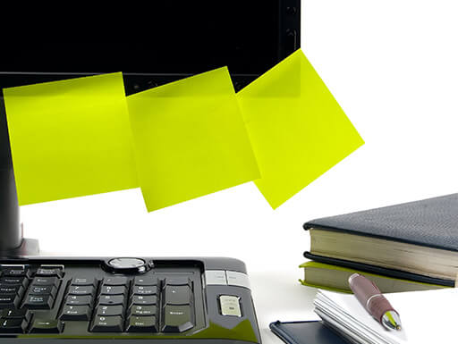 black keyboard, books and black computer monitor with 3 lime green disorganized sticky notes