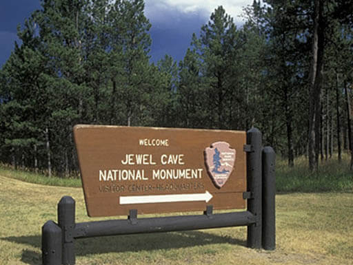 The fence post sign reading: Jewel Cave National Monument sits beneath a cloudy sky on a summer afternoon with tall green trees in the background