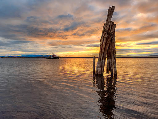 Colorful sunset with boat in background over Lake Champlain in Burlington, Vermont.
