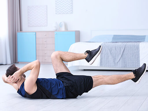 """=""""A man wearing athletic clothes does bicycle crunches on the floor of his hotel room during an indoor bodyweight workout session."""