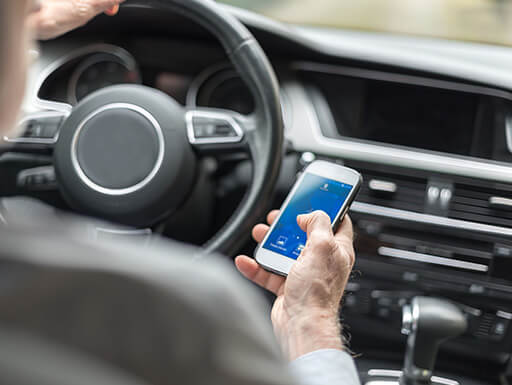 A man uses a smartphone while driving a car during the daytime.