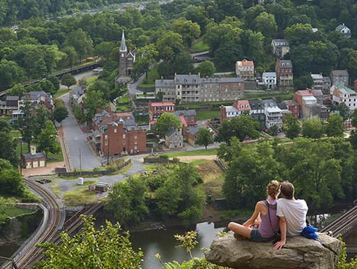 Couple sitting on a boulder high on the hills overlooking Harpers Ferry.