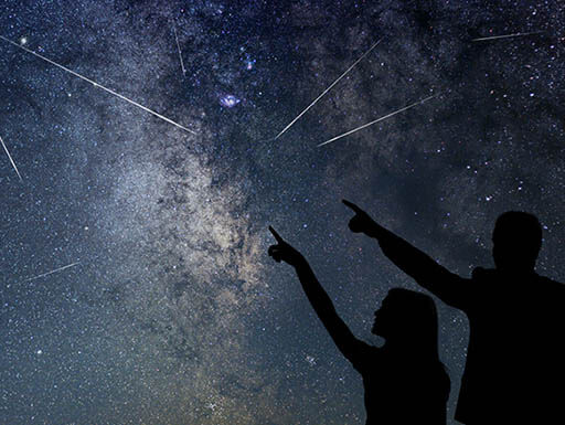 Silhouette of father and daughter watching and pointing at a meteor shower at night