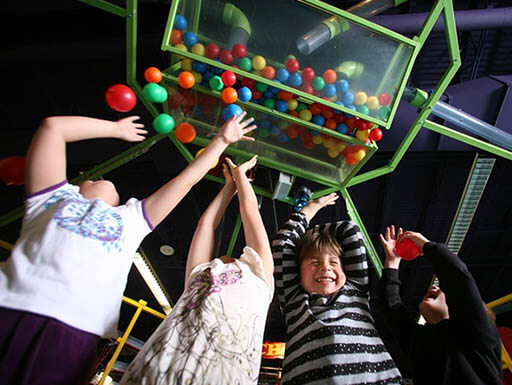 Kids with colorful balls in the air at the Omaha Children's Museum