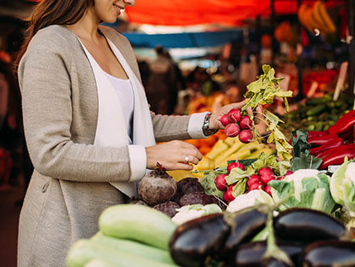 A customer holds fresh vegetables at a farmer's market on a cloudy morning.