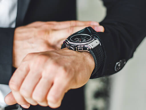 View of a Businessman's hands in a suit as he checks his watch for time